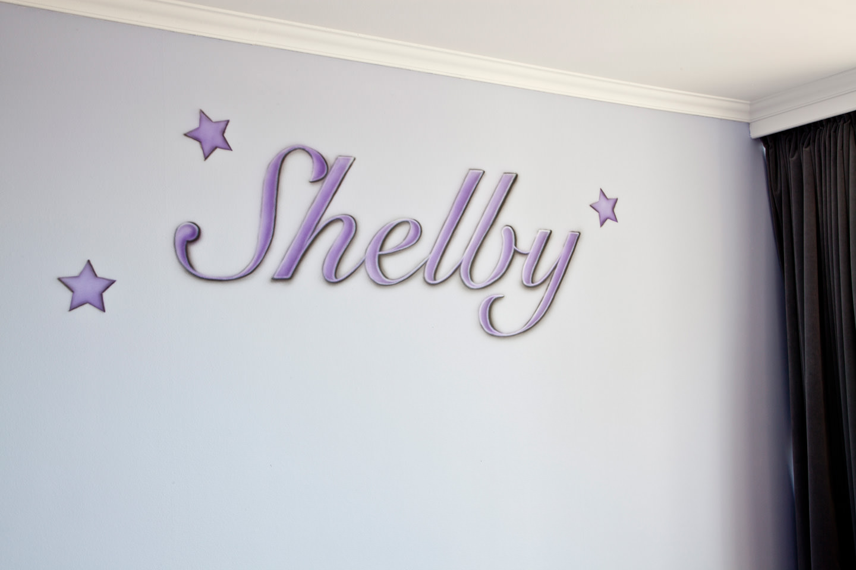 Paarse airbrush naam schildering met sterretjes in babykamer