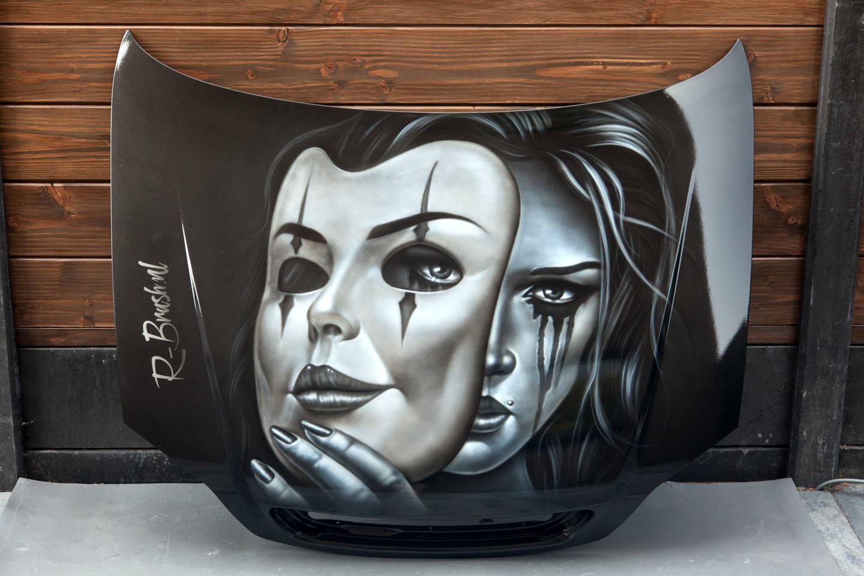 Airbrush schildering in grijstinten op zwarte motorkap.