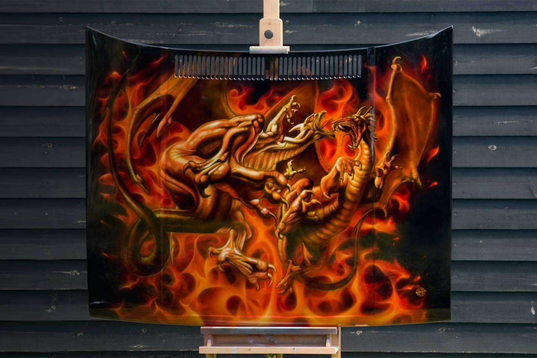 Custom painting vechtende draken en true fire op zwarte motorkap.