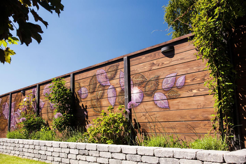 schildering buiten op schutting gekleurde bladeren